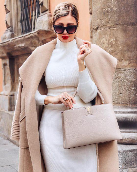 Mujer rubia con vestido blanco y lentes de sol modelando en la calle