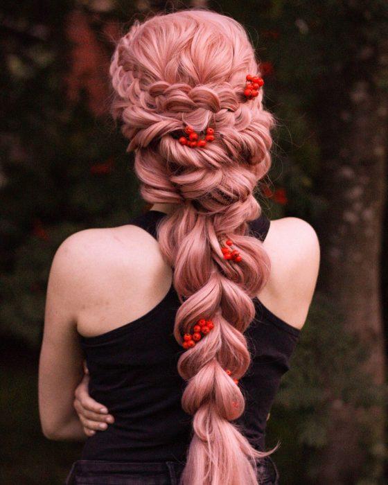 Chica de cabello rosa con trenza adornada con flores