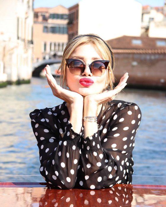 Mujer rubia con lentes de sol y blusa polka dots frente a calle en Venecia con pose de beso