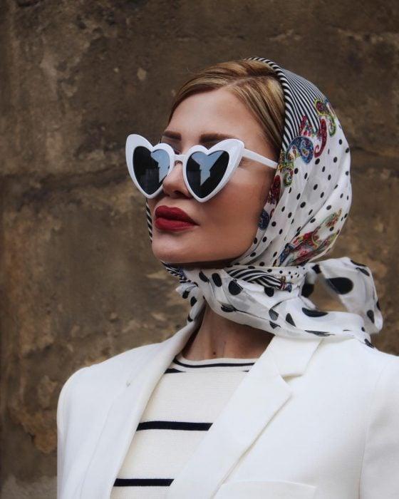 Mujer rubia con bandana en la cabeza y lentes de sol en forma de corazón
