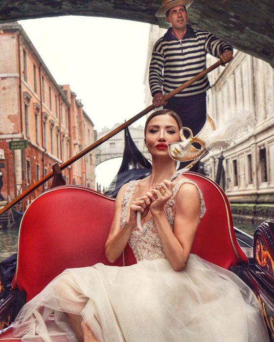 Mujer rubia con vestido blanco de tul y máscara de carnaval paseando en góndola en Venecia