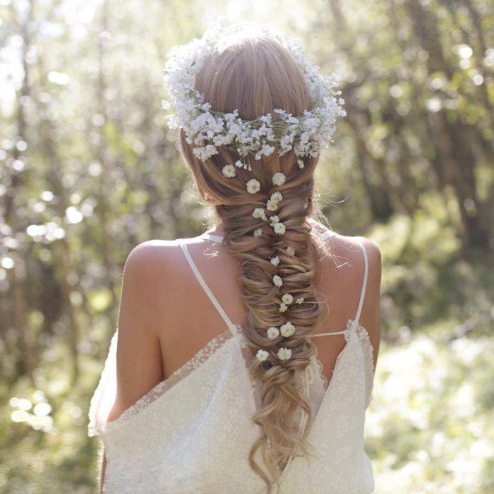 Chica rubia con trenza de espiga adornada con corona de flores blancas