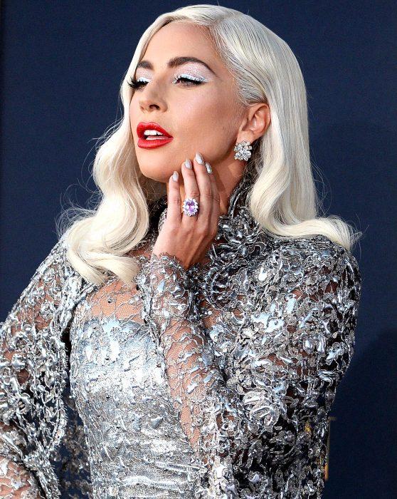 Lady Gaga en la premiere de A Star is a born sujetando posando para las cámaras mientras tiene su mano en el mentón para mostrar su anillo de compromiso