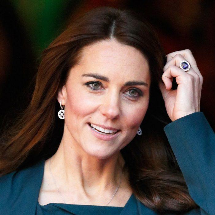 Kate Middleto usando un vestido verde mientras camina por la calle y se sujeta el cabello para mostrar su anillo de compromiso