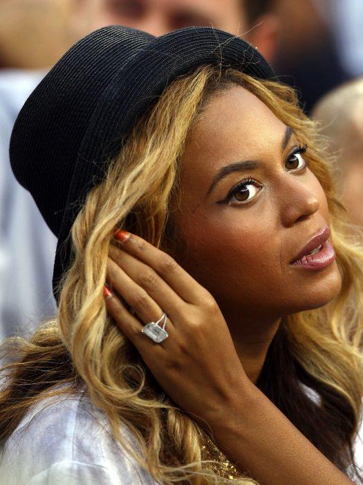 Beyonce usando un sombrero negro y tomando su cabello con las manos mientras muestra ligeramente su anillo de compromiso, un diamante cuadrado.