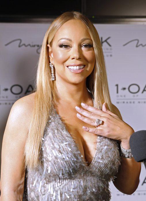 Mariah Carey dando una entrevista y poniendo su mano sobre su pecho para mostrar su anillo de compromiso