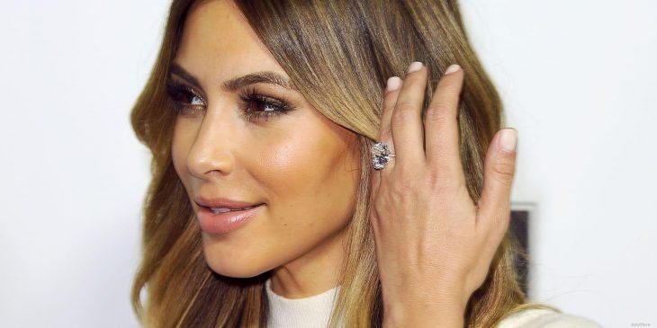 Kim Kardashian sujetando su cabello mientras muestra ligeramente su anillo de compromiso
