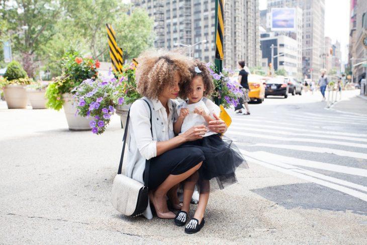 Mamá e hija de cabello rizado, usando cada quien una falda negra, chamarra de mezclilla, paradas en medio de la avenida, posando para una foto familiar