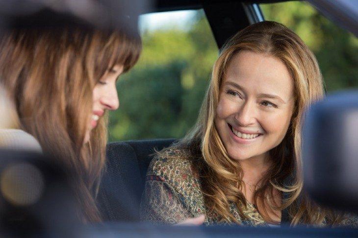 Mamá e hija charlando dentro de un automóvil, ambas sonriendo, mirándose a los ojos, con cabello hasta los hombros en tonos dorados, ojos amielados, labios delgados, baradas en medio del bosque