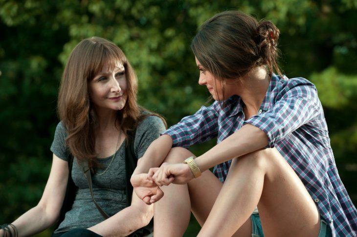 Mamá e hija sentadas en un bosque a la orilla del río, mirándose a los ojos, una con cabello recogido, la otra de cabello suelto, ambas sonriendo y charlando amenamente
