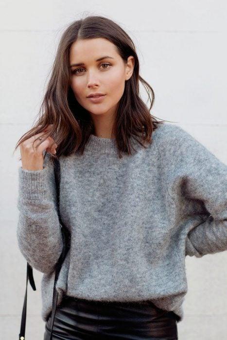Chica con cabello castaño al hombro, long bob, suéter gris