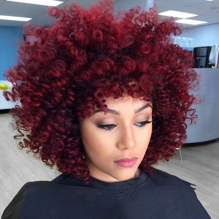 Chica con cabello rojo borgoña chino tipo afro