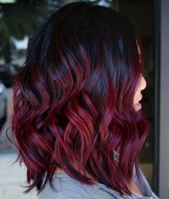 Chica con cabello rojo borgoña y chino