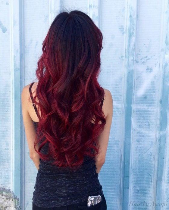Chica con cabello rojo borgoña ondulado