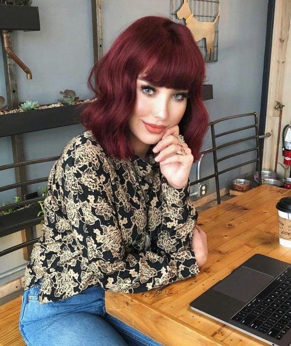 Chica con cabello rojo borgoña sentada en un restaurante