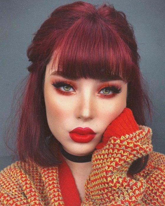 Chica con cabello rojo borgoña con fleco