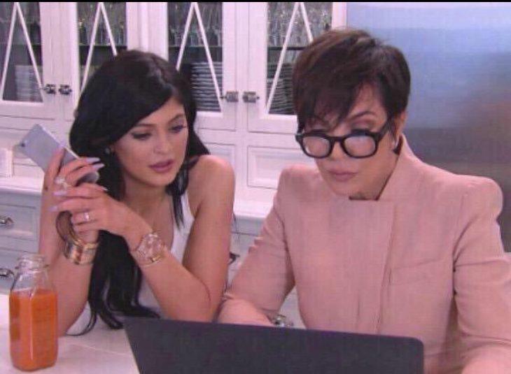 Kendall Jenner sentada junto a su madre en la mesa de la cocina viendo como escribe cosas en su computadora