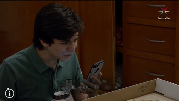 Escena de la serie La rosa de Guadalupe en la que un chico está viendo su celular mientras está sentado frente a una caja de pizza