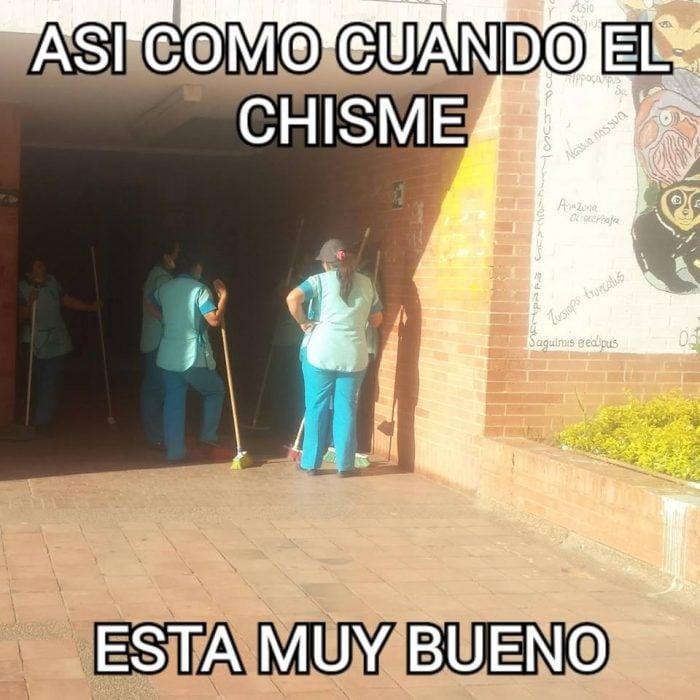 Meme de señoras de la limpieza sujetando sus escobas y reunidas en la puerta de una escuela conversando