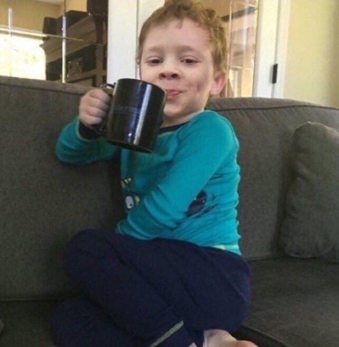 Gavin, niño de los memes, sentado en un sofá con las piernas cruzadas y tomando una taza de café