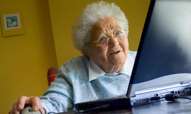 Mujer de la tercera edad con cara de intriga frente a una computadora sosteniendo un mouse