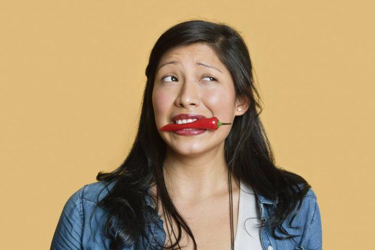 Chica con un chile rojo en la boca