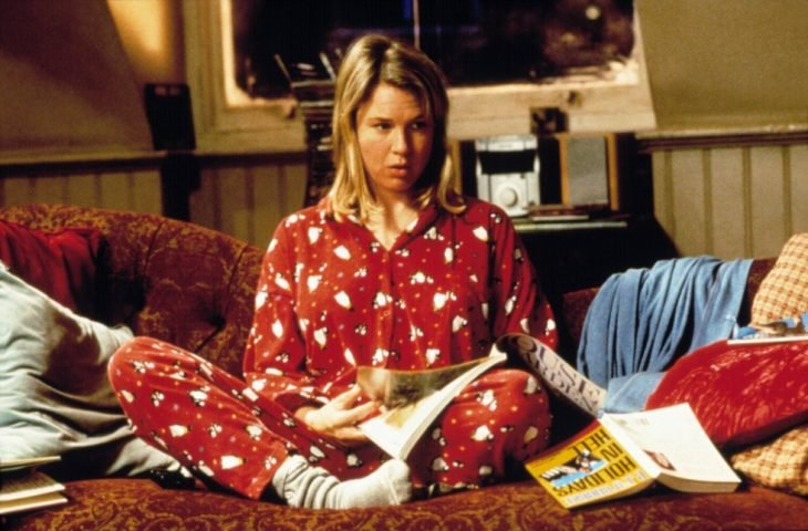 Escena de chica en pijama sentada en un sillón leyendo una revista de la película el diario de Bridget Jones