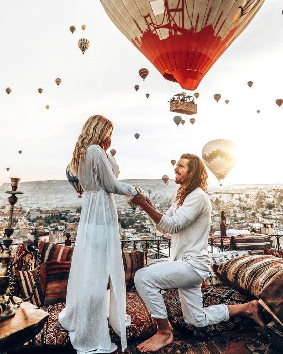 Novio de cabello largo hincado pidiéndole matrimonio a su novia de cabello rubio, ambos vestidos de blanco con globos aerostáticos en el fondo