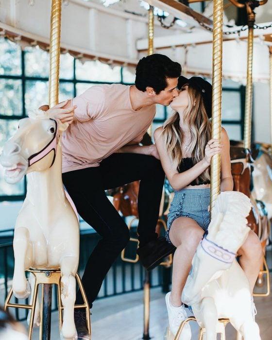 Pareja de novios besándose en un carrusel sobre caballos de juguete blancos