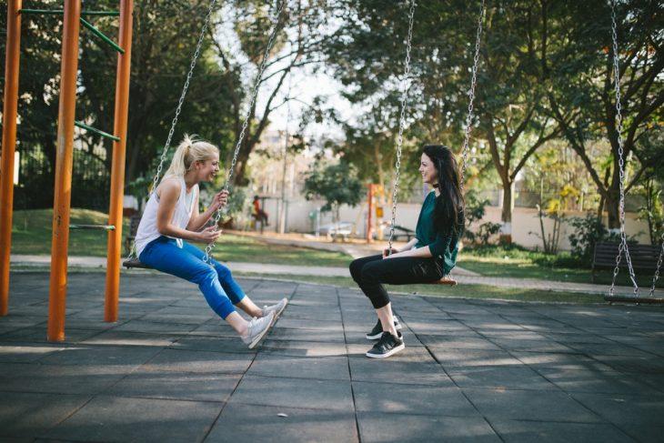 Dos chicas en un parque, sentadas en un columpio, comiendo helado, charlando, al atardecer