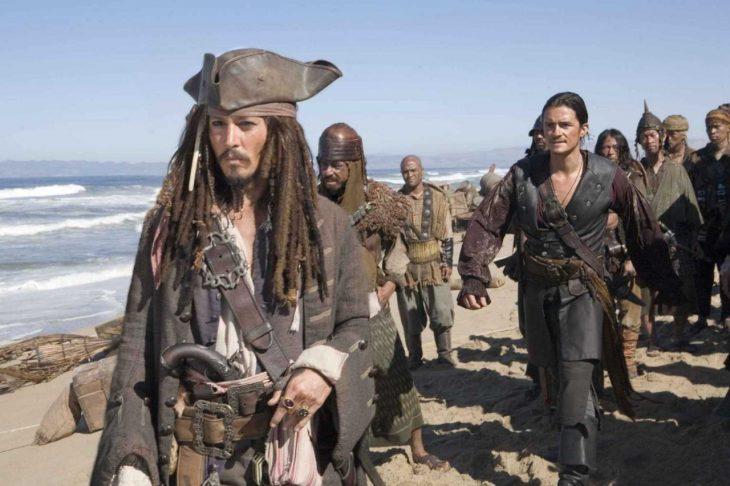 Escena de piratas caminando por la playa en la película Piratas del Caribe: El cofre de la muerte