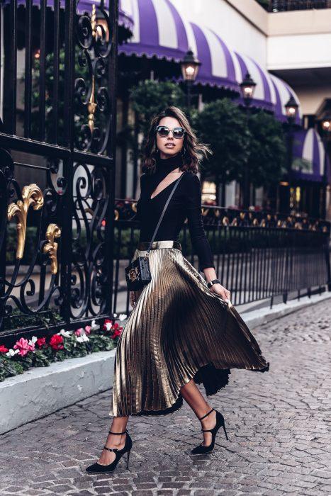 Chica usando una falda larga mientras posa para una foto en la calle