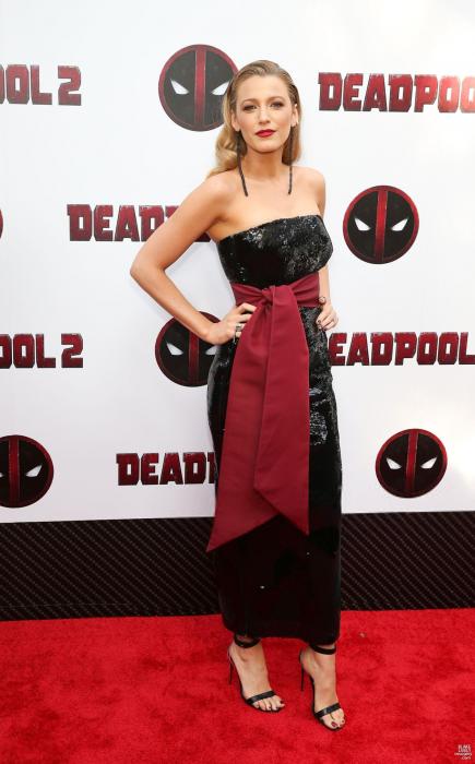 Blake Lively usando un vestido negro con cinturón rojo en la algombra roja de Deadpol 2