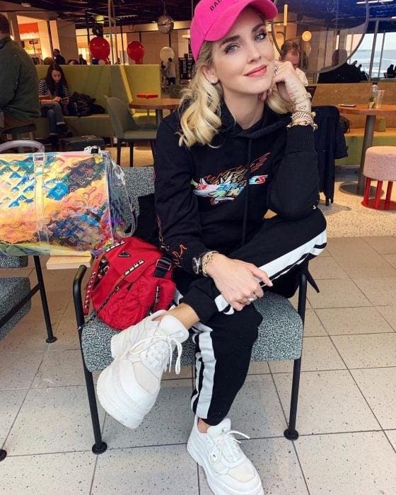 Chiara Ferragni sentada en un café usando un outfit relajado de pants, gorra rosa y tenis Fila