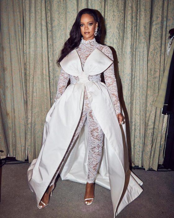 Rihanna usando un atuendo blanco con un moño grande mientras posa para una foto en Instagram