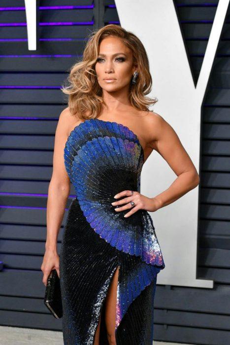 Jennifer Lopez usando un vestido azul con tonos negros en la alfombra roja de la after party de Vanity Fair en los óscar 2019