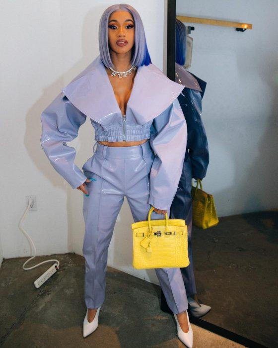 Cardi B usando un traje morado con una bolsa de color amarillo meintras posa para una foto de Instagram