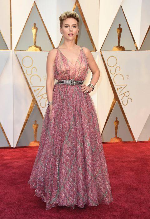 Scarlett Johansson usando un vestido rosa con toques plateados durante la alfombra roja de los premios Óscar