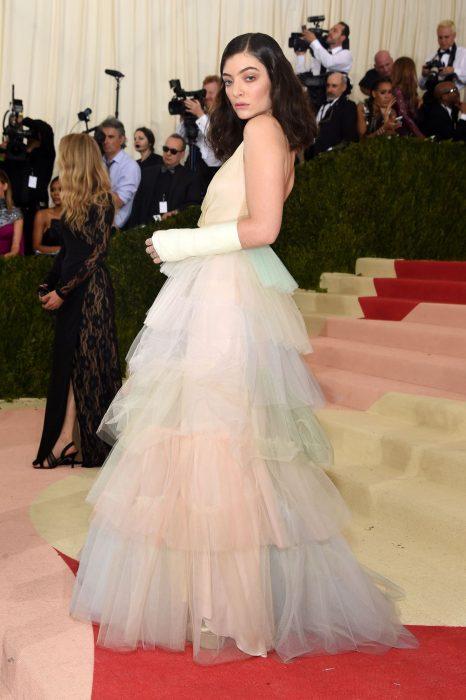Cantante Lorde usando un vestido de capas en colores pastel en la alfombra roja de los Met Gala