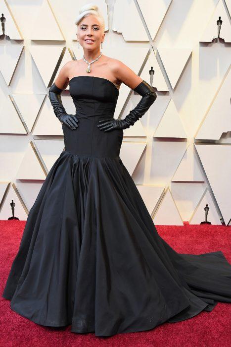 Lady Gaga usando un vestido negro de gala con guantes en la alfombra roja de los premios Óscar 2019