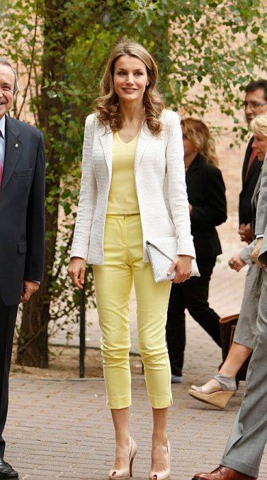 Reina Letizia Ortiz caminando por las caslles mientras usa un atuendo amarillo y un blazer de color hueso