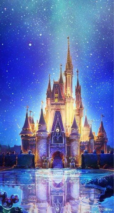 Fondo de pantalla de celular que tiene el castillo de Disney iluminado con colores blancos y azules