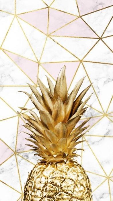 Fondo de pantalla de celular que tiene una piña en color dorado con triángulos de mármol blanco y rosa