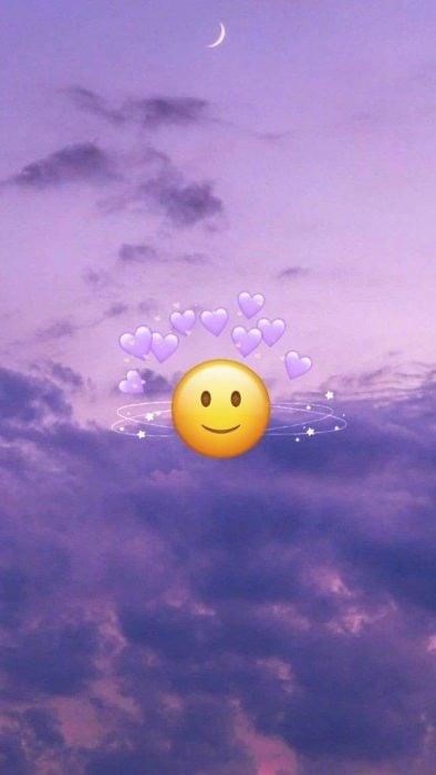 Fondos de pantalla para celular, wallpaper de emoji de carita feliz con corazones morados en cielo con nubes moradas