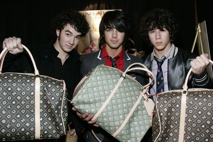 chicos llevando bolsos de mano