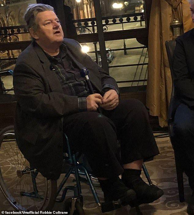 El actor Robbie Coltrane sentado en una silla de ruedas para promover un juego en universal studios