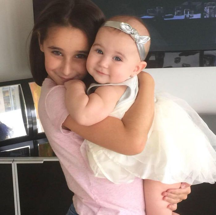 Hermana mayor cargando a hermana menor
