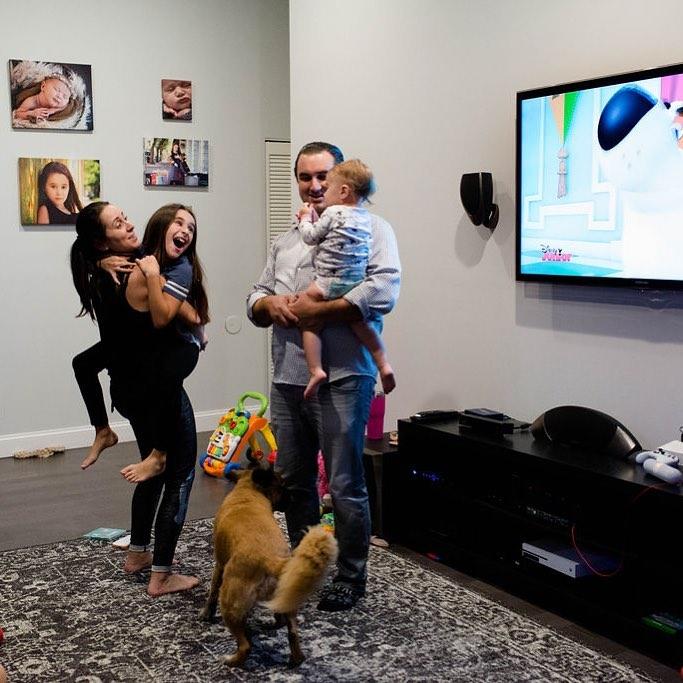 Mamá, papá e hijas en la sala de estar con perro