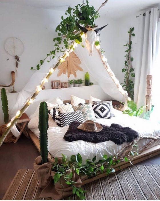 Habitación decorada con un tipi en el centro de la cama y sobre él se encuentran plantas verdes que ayudan a decorar el espacio en blanco
