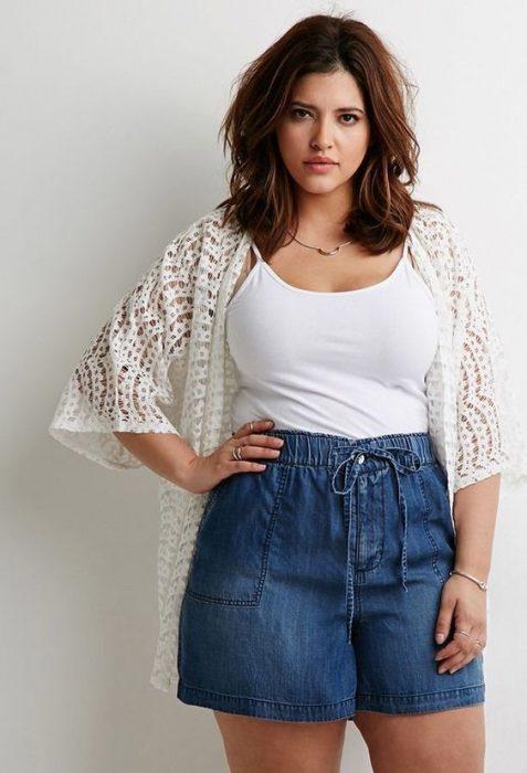 Chica modelando un short holgado de mezclilla y un blusa de tirantes blanca